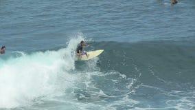 Ένα surfer οδηγά ένα κύμα στην κυματωγή στο ωκεάνιο μπλε στο σημείο κυματωγών απόθεμα βίντεο