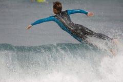 Ένα surfer φαίνεται να πετά πέρα από ένα κύμα στοκ εικόνες