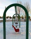 Ένα swingset χιονισμένο πέρα από την παιδική χαρά στοκ εικόνα