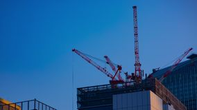 Ένα timelapse των γερανών στην κατώτερη κατασκευή πίσω από το μπλε ουρανό στο Τόκιο απόθεμα βίντεο