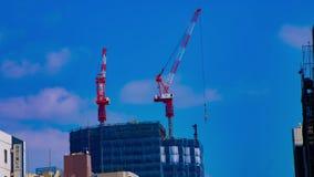 Ένα timelapse των γερανών στην κατώτερη κατασκευή πίσω από το μπλε ουρανό στο Τόκιο φιλμ μικρού μήκους