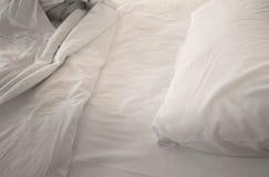 Ένα unmade κρεβάτι με τα άσπρα linens Στοκ Φωτογραφίες
