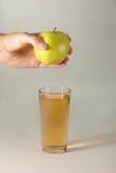 Ένα woman& x27 το χέρι του s συμπιέζει το φρέσκο χυμό Καθαρή έκχυση χυμού μήλων έξω από τα φρούτα στο γυαλί Στοκ Φωτογραφία