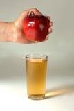 Ένα woman& x27 το χέρι του s συμπιέζει το φρέσκο χυμό Καθαρή έκχυση χυμού μήλων έξω από τα φρούτα στο γυαλί Στοκ Φωτογραφίες