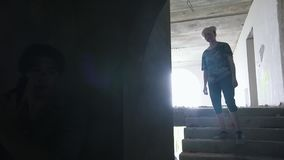 Ένα zombie που περπατούν στα σκαλοπάτια και ένας επιζών ατόμων που στοχεύει με ένα πυροβόλο όπλο σε τους απόθεμα βίντεο