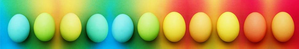 Ένδεκα βιολογικά οργανικά μπλε τυρκουάζ πράσινο μήλου κίτρινα αυγά Πάσχας σε ένα υπόβαθρο ουράνιων τόξων στοκ εικόνα με δικαίωμα ελεύθερης χρήσης