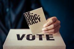 Ένθετο καφετιού εγγράφου στο κιβώτιο ψηφοφορίας, έννοια δημοκρατίας στοκ φωτογραφίες