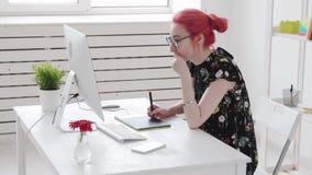 Έννοια ή της εργασίας γραφείων Νέος θηλυκός φωτογράφος, retoucher ή γραφικός σχεδιαστής με τις χρωματισμένες εργασίες τρίχας απόθεμα βίντεο