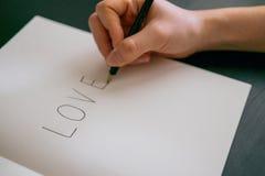 Έννοια αγάπης - αγάπη γραψίματος χεριών στο βιβλίο Στοκ εικόνες με δικαίωμα ελεύθερης χρήσης