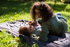 Έννοια αγάπης, σχέσης, οικογενειών και ανθρώπων - χαμογελώντας ζεύγος που βρίσκεται στο πάρκο φθινοπώρου στοκ εικόνες