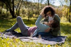 Έννοια αγάπης, σχέσης, οικογενειών και ανθρώπων - χαμογελώντας ζεύγος που βρίσκεται στο πάρκο φθινοπώρου στοκ εικόνα με δικαίωμα ελεύθερης χρήσης