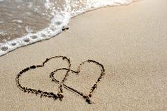 Έννοια αγάπης - δύο καρδιές που επισύρονται την προσοχή στην άμμο παραλιών Στοκ Εικόνα