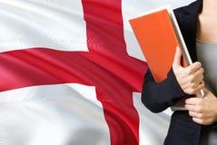 Έννοια αγγλικής γλώσσας εκμάθησης Νέα γυναίκα που στέκεται με τη σημαία της Αγγλίας στο υπόβαθρο Βιβλία εκμετάλλευσης δασκάλων, π στοκ εικόνα