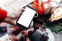 Έννοια αγορών Χριστουγέννων Τηλέφωνο εκμετάλλευσης χεριών με την κενή οθόνη Στοκ Εικόνα