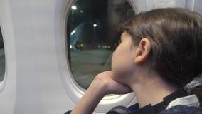 Έννοια αεροσκαφών αεροπορίας κοριτσιών εφήβων το νέο κορίτσι φαίνεται έξω η συνεδρίαση αεροπλάνων από το παράθυρο πτήση τη νύχτα  απόθεμα βίντεο