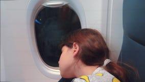 Έννοια αεροσκαφών αεροπορίας Νέος ύπνος μικρών κοριτσιών στη συνεδρίαση αεροπλάνων από το παράθυρο Τρόπος ζωής πτήσης τη νύχτα απόθεμα βίντεο