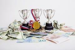 Έννοια αθλητικής νίκης: τρία φλυτζάνια μεταξύ του διαφορετικού ευρώ νομισμάτων, δολάριο, rubl, πρώτη θέση χρυσών μεταλλίων Στοκ Εικόνες