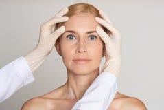 Έννοια αισθητικής χειρουργικής Γιατρός που εξετάζει το ώριμο πρόσωπο γυναικών στοκ φωτογραφία με δικαίωμα ελεύθερης χρήσης