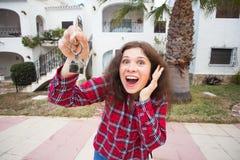 Έννοια ακίνητων περιουσιών και ιδιοκτησίας Ευτυχής ιδιοκτησία Η ελκυστική νέα εκμετάλλευση γυναικών κλειδώνει στεμένος υπαίθρια ε στοκ φωτογραφία με δικαίωμα ελεύθερης χρήσης