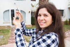 Έννοια ακίνητων περιουσιών και ιδιοκτησίας Ευτυχής ιδιοκτησία Η ελκυστική νέα εκμετάλλευση γυναικών κλειδώνει στεμένος υπαίθρια ε στοκ φωτογραφίες με δικαίωμα ελεύθερης χρήσης