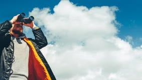 Έννοια αναζήτησης ταξιδιού Πεζοποριες άτομο που κοιτάζει μέσω των διοπτρών στην απόσταση ενάντια στον ουρανό Χαμηλός βλαστός σημε Στοκ Εικόνες