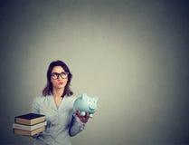 Έννοια δανείου σπουδαστών Γυναίκα με το σωρό των βιβλίων και το piggy σύνολο τραπεζών του χρέους που ξανασκέφτεται τη μελλοντική  Στοκ Φωτογραφίες