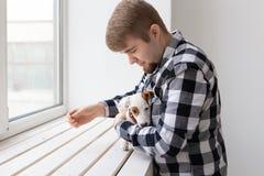 Έννοια ανθρώπων και κατοικίδιων ζώων - ευτυχές άτομο που κρατά ένα τεριέ του Jack Russell σκυλιών πέρα από το υπόβαθρο παραθύρων στοκ φωτογραφία