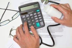 Έννοια δαπανών και αμοιβών υγειονομικής περίθαλψης Το χέρι του έξυπνου γιατρού χρησιμοποίησε ένα ασβέστιο στοκ εικόνα