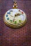 Έννοια αποκάλυψης - διακοσμητικό ρολόι τσεπών σε έναν κόκκινο τοίχο τούβλων με το ξεφλουδισμένο χρώμα Στοκ Εικόνα