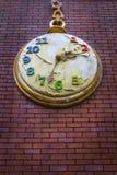 Έννοια αποκάλυψης - διακοσμητικό ρολόι τσεπών σε έναν κόκκινο τοίχο τούβλων με το ξεφλουδισμένο χρώμα Στοκ εικόνες με δικαίωμα ελεύθερης χρήσης