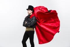 Έννοια αποκριών βαμπίρ - πορτρέτο του όμορφου καυκάσιου κοστουμιού αποκριών βαμπίρ που κυματίζει τον κόκκινο, μαύρο επενδύτη του Στοκ Φωτογραφίες
