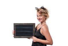 Έννοια αποκριών, γυναίκα με τα αυτιά γατών καρναβαλιού που κρατά τον πίνακα κιμωλίας Στοκ Φωτογραφία