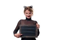 Έννοια αποκριών, γυναίκα με τα αυτιά γατών καρναβαλιού που κρατά τον πίνακα κιμωλίας Στοκ Φωτογραφίες