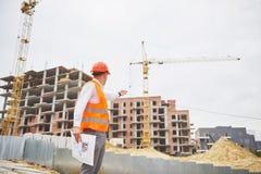Έννοια αρχιτεκτονικής και εγχώριας ανακαίνισης - άτομο στο κράνος και γάντια με το σχεδιάγραμμα στο εργοστάσιο στοκ εικόνα