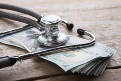 έννοια ασφάλειας υγείας - στηθοσκόπιο πέρα από τα χρήματα στοκ εικόνα με δικαίωμα ελεύθερης χρήσης