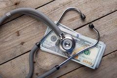 έννοια ασφάλειας υγείας - στηθοσκόπιο πέρα από τα χρήματα στοκ εικόνα