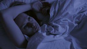 Έννοια αϋπνίας Η γυναίκα στο κρεβάτι δεν μπορεί τη νύχτα να κοιμηθεί
