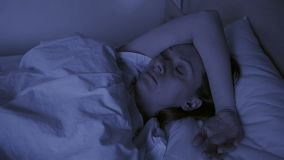 Έννοια αϋπνίας Η γυναίκα στο κρεβάτι δεν μπορεί τη νύχτα να κοιμηθεί φιλμ μικρού μήκους