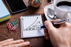 Έννοια αύξησης τιμών κατοικίας σχεδίων προσώπων στο σημειωματάριο Στοκ εικόνα με δικαίωμα ελεύθερης χρήσης
