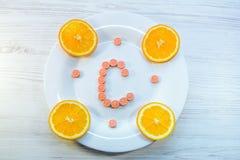 Έννοια βιταμίνης C - χάπια και πορτοκαλιές φέτες Στοκ Εικόνα