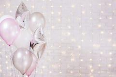 Έννοια γενεθλίων και Χριστουγέννων - κλείστε επάνω των μπαλονιών αέρα πέρα από το υπόβαθρο τουβλότοιχος με τα φω'τα στοκ φωτογραφία