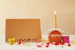 Έννοια γενεθλίων με το cupcake και το κερί δίπλα στη ευχετήρια κάρτα Στοκ φωτογραφία με δικαίωμα ελεύθερης χρήσης