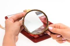 Έννοια για Διαδίκτυο που ψωνίζει: χέρια με Magnifier και τη τιμή Στοκ Φωτογραφία