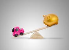 Έννοια για την αποταμίευση για να αγοράσει το αυτοκίνητο με το piggy παιχνίδι τραπεζών και αυτοκινήτων seesaw Στοκ Εικόνες