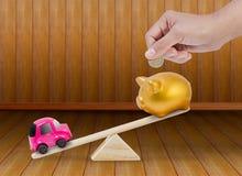 Έννοια για την αποταμίευση για να αγοράσει το αυτοκίνητο με το piggy παιχνίδι τραπεζών και αυτοκινήτων seesaw Στοκ εικόνα με δικαίωμα ελεύθερης χρήσης