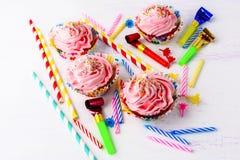 Έννοια γιορτής γενεθλίων με τα διακοσμημένα ρόδινα cupcakes και τα κεριά Στοκ εικόνες με δικαίωμα ελεύθερης χρήσης