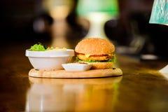 Έννοια γρήγορου φαγητού Burger με το κρέας και τη σαλάτα τυριών Εξαπατήστε το γεύμα Εύγευστο burger με τους σπόρους σουσαμιού Bur στοκ εικόνες