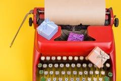 Έννοια διακοπών - γραφομηχανή με το κενό έγγραφο τεχνών, κιβώτια δώρων για το κίτρινο υπόβαθρο Στοκ εικόνες με δικαίωμα ελεύθερης χρήσης