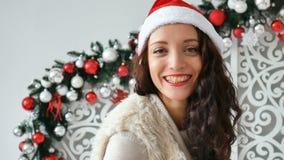 Έννοια διακοπών και ανθρώπων - όμορφη γυναίκα στο καπέλο santa και και τη σγουρή τρίχα που χαμογελά ενάντια στο σκηνικό φιλμ μικρού μήκους