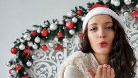 Έννοια διακοπών και ανθρώπων - όμορφη γυναίκα στο καπέλο santa και και τη σγουρή τρίχα που χαμογελά ενάντια στο σκηνικό απόθεμα βίντεο
